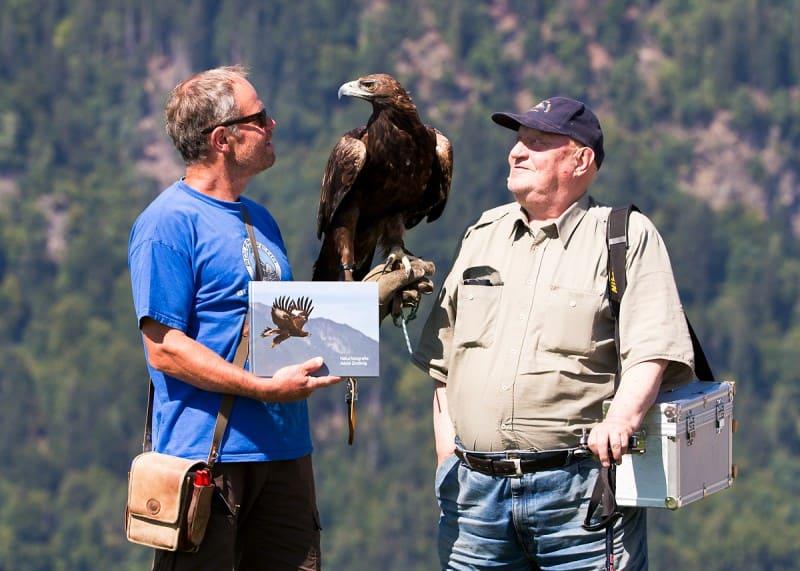 Franz Schüttelkopf mit Jubiläumsbuch 'Naturfotografie Jakob Zmölnig' , einem unserer Adler und Jubilar Jakob Zmölnig. © Michael Rzepa